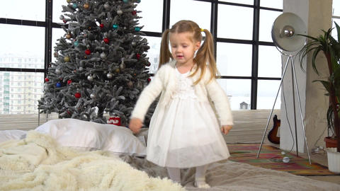 Funny jumping little girl dressed in white dress with Christmas tree behind her Live Action