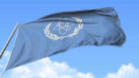 Waving flag of the International Atomic Energy Agency IAEA, low angle view Live Action