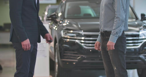 Close-up of unrecognizable male Caucasian dealer giving car keys to male Live Action