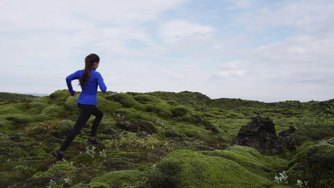 Trail running woman in cross country run. Female runner training jogging outdoor Live Action