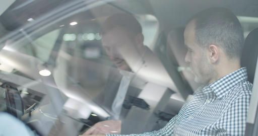 Shooting through car side window of mature Caucasian car dealer explaining Live Action