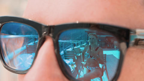 Female reflection in mirrored sunglasses close up. Flirting playful woman in Live Action