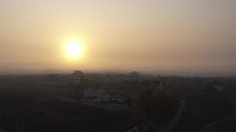 The bright sun shines over a small town on an autumn morning. Morning foggy sky Live Action
