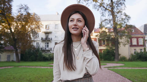 Carefree lovely good-looking woman in stylish hat talking on phone while Live Action