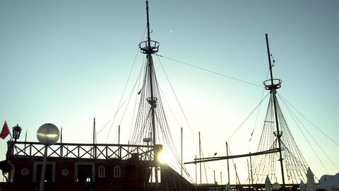 A pirate ship stands at the pier in the bay. Old wooden ship. An elephant shines Live Action