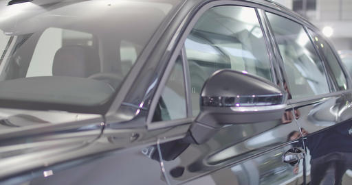Close-up of new black automobile standing in car dealership or in the parking Live Action