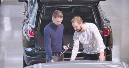 Top view op Caucasian car dealer and male client examining car bumper. Trader Live Action