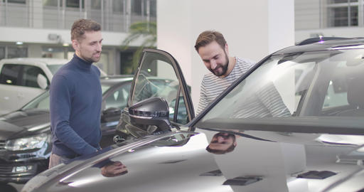 Male Caucasian car dealer opening car door, adult man sitting into salon. Young Live Action