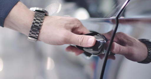Close-up of black car door handle opened by male Caucasian hand, man sitting Live Action