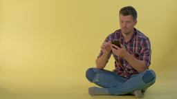 Handsome boy sitting on the floor and chatting with friends on smartphone Live Action