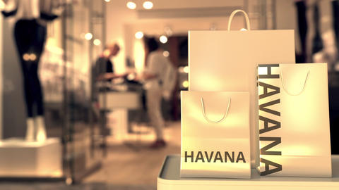 Paper shopping bags with Havana caption against blurred store entrance. Retail Live Action