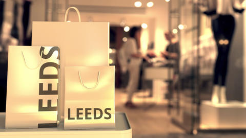 Shopping bags with Leeds caption against blurred store entrance. Retail in the Live Action