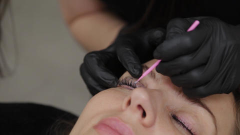 Professional beautician in a beauty salon straightens eyelashes to a client Live Action