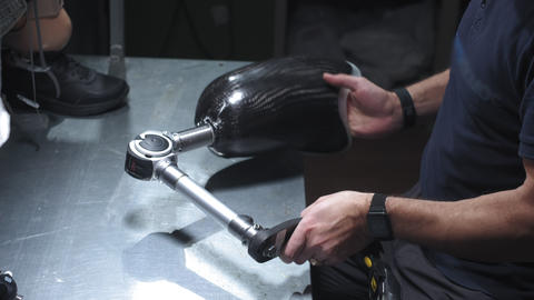 Production of a prosthetic leg. A man creates part of the leg. An engineer is Live Action