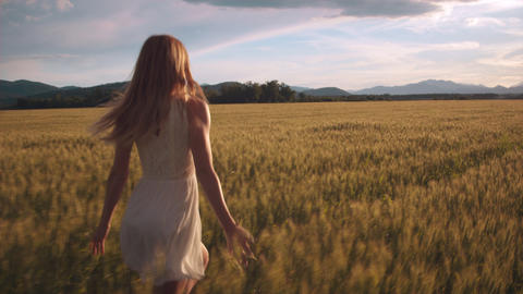 Pretty girl in a white dress running through field and touching wheat heads Footage