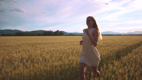 Slowmo - In front of a girl running through field and touching wheat heads Footage