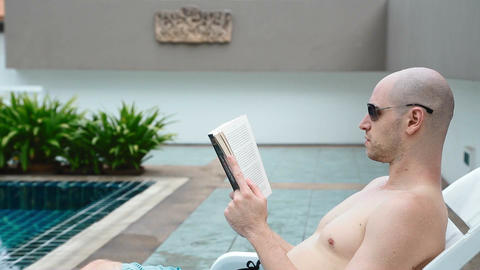 bald white man with sunglasses reads book at pool Live影片
