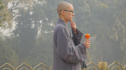 Young monk in grey robe prays with praying wheel,Kushinagar,India Footage