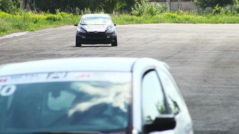 Steering race cars and track tarmac, drivers pass by Footage
