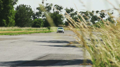 Car roars near by growing wheat field during sport racing laps Footage