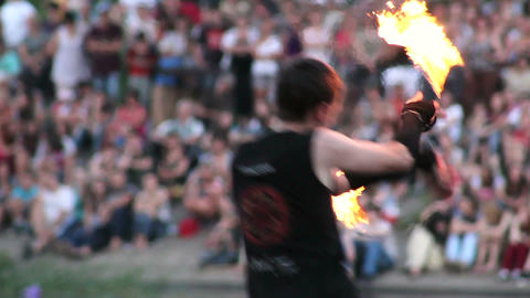 Young male artist with chained fire pois in front of audience spinning swinging Footage