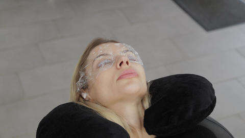 Beautiful woman with film on her eyes in a beauty parlor Live Action