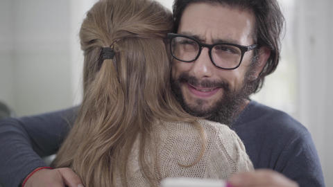 Close-up face of young Caucasian man with black beard imitating joy as his wife Live Action