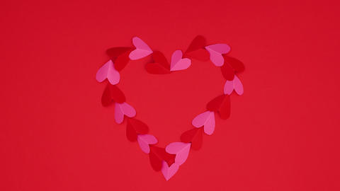 Valentine's day heart made of little red and pink hearts disappear and appear on red background - Animation