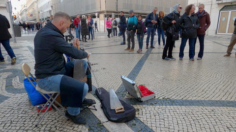 Street musician playing music on a saw at famous Augusta street in Lisbon - CITY Live Action