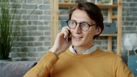 Young brunet chatting on mobile phone in apartment enjoying conversation Live Action