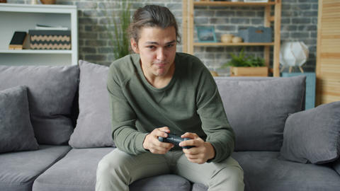 Emotional young man playing video game at home sitting on sofa at home Live Action