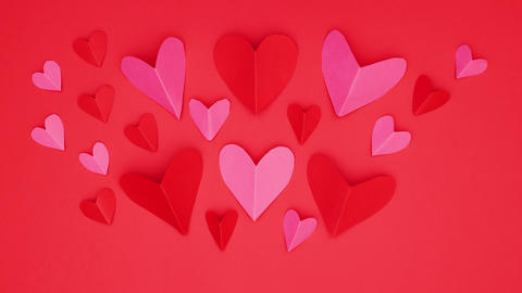 Red and pink hearts appear on red background - Stop motion Valentine's day Animation
