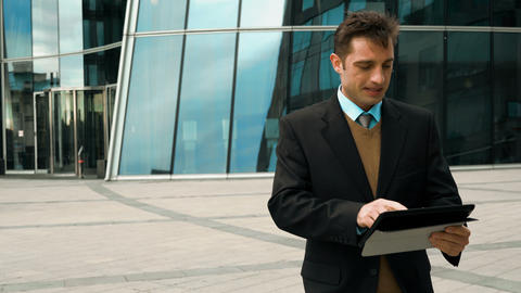 Businessman using electronic tablet outside a building Live Action