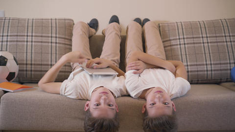 Two Caucasian twin brothers laying laying upside down on sofa, looking at camera Live Action