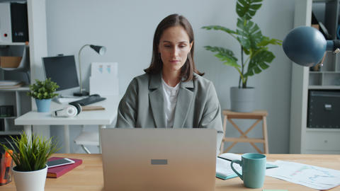 Female office worker using laptop then drinking tea in workplace relaxing Live Action