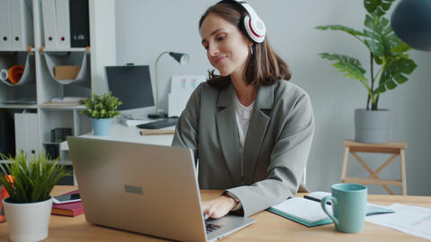 Playful lady listening to music in headphones dancing working with laptop having Live Action