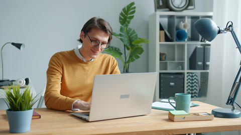 Cheerful guy using laptop typing working at table in office concentrated on job Live Action