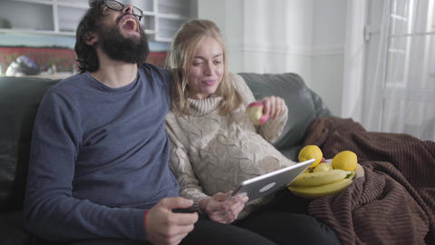 Cheerful married couple looking at tablet screen and laughing out loud. Pregnant Live Action