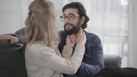 Close-up of cheerful Caucasian couple discussing man's beard style. Young blond Live Action