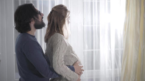 Side view of bearded Caucasian man with black hair kissing wife's head and Live Action