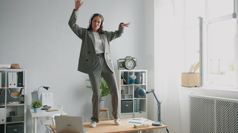 Beautiful office worker in suit dancing on desk in office wearing headphones Live Action