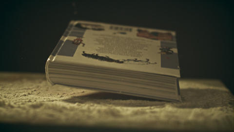 Super slow motion shot of a book falling down on a dusty wooden table, close-up Live Action
