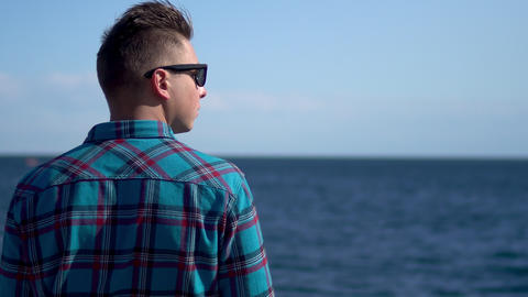 A young man looks at the sea. A man in a blue shirt admires nature. A man stands Live Action