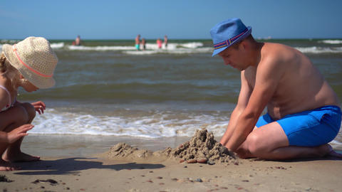 Fat father with hat and little playful daughter building castle from wet sand Live Action