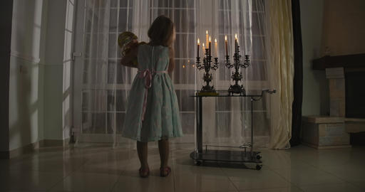 Back view of little Caucasian girl standing in candlelight with doll. Child Live Action