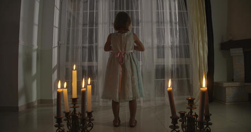 Back view of strange Caucasian girl standing in candlelight. Weird child turning Live Action