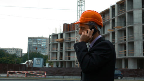Builder in helmet talking on a smart phone Live Action