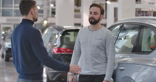 Back side view of Caucasian car dealer in casual clothes giving car keys to Live Action