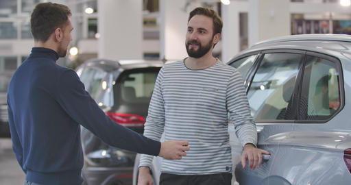 Portrait of two Caucasian men standing in car dealership, exhanging keys from Live Action
