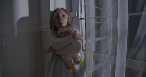 Close-up of scared Caucasian blond girl hugging doll and yelling. Portrait of Live Action